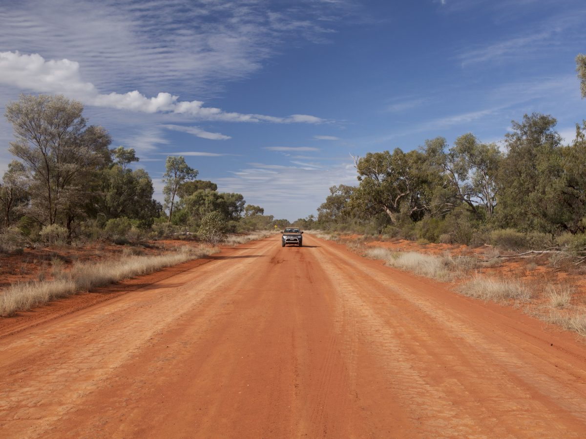 Car on an unsealed red dirt road in outback NSW
