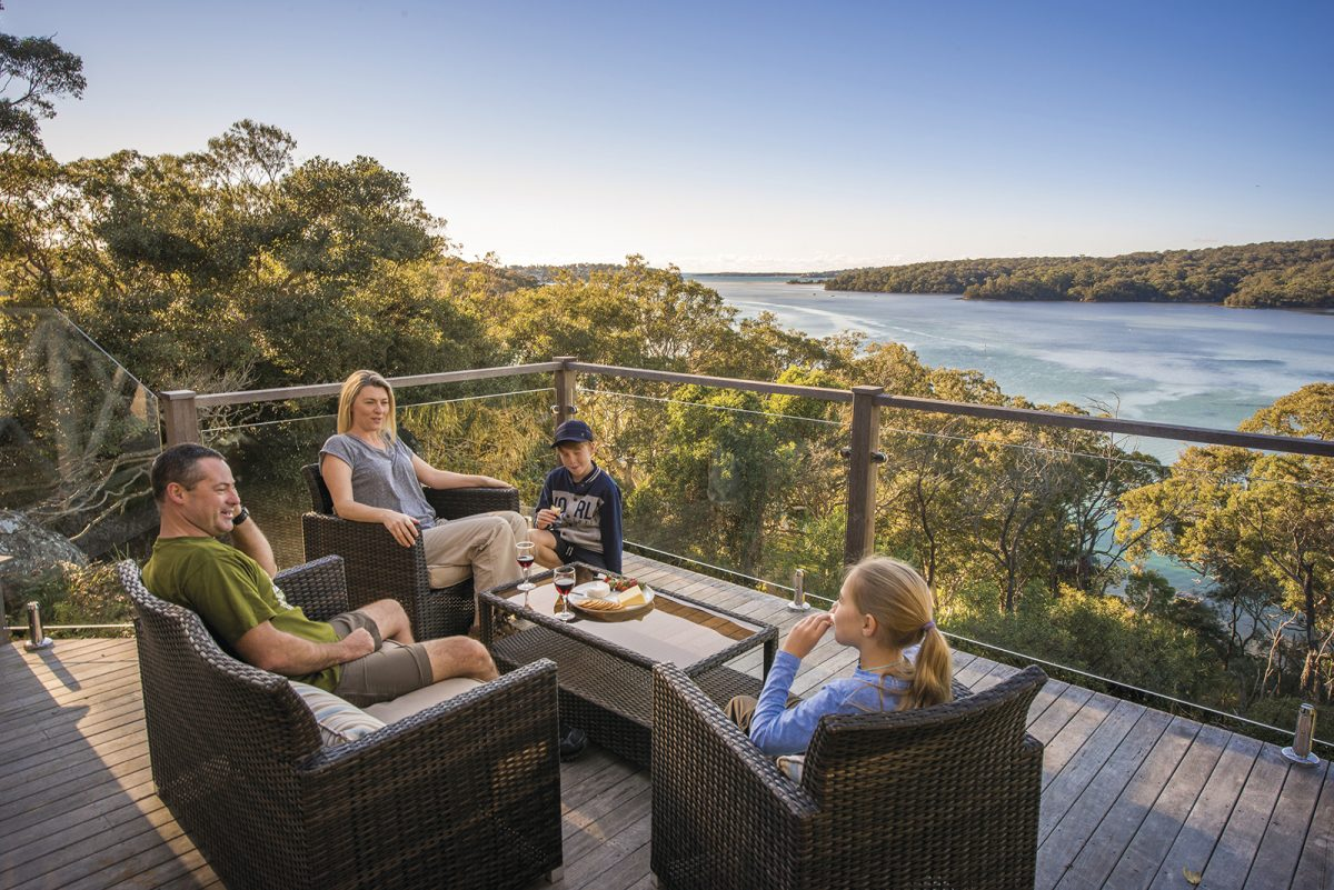 A family of four on the deck of Hilltop cottage, Royal National Park