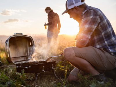 A young couple cooking hamburgers on a portable barbecue