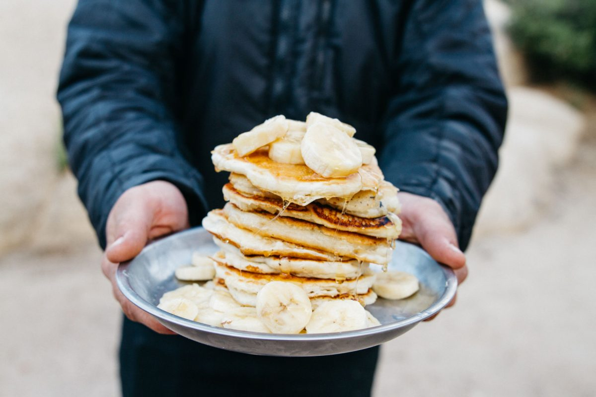 A man presents a plate containing pancakes and banana slices