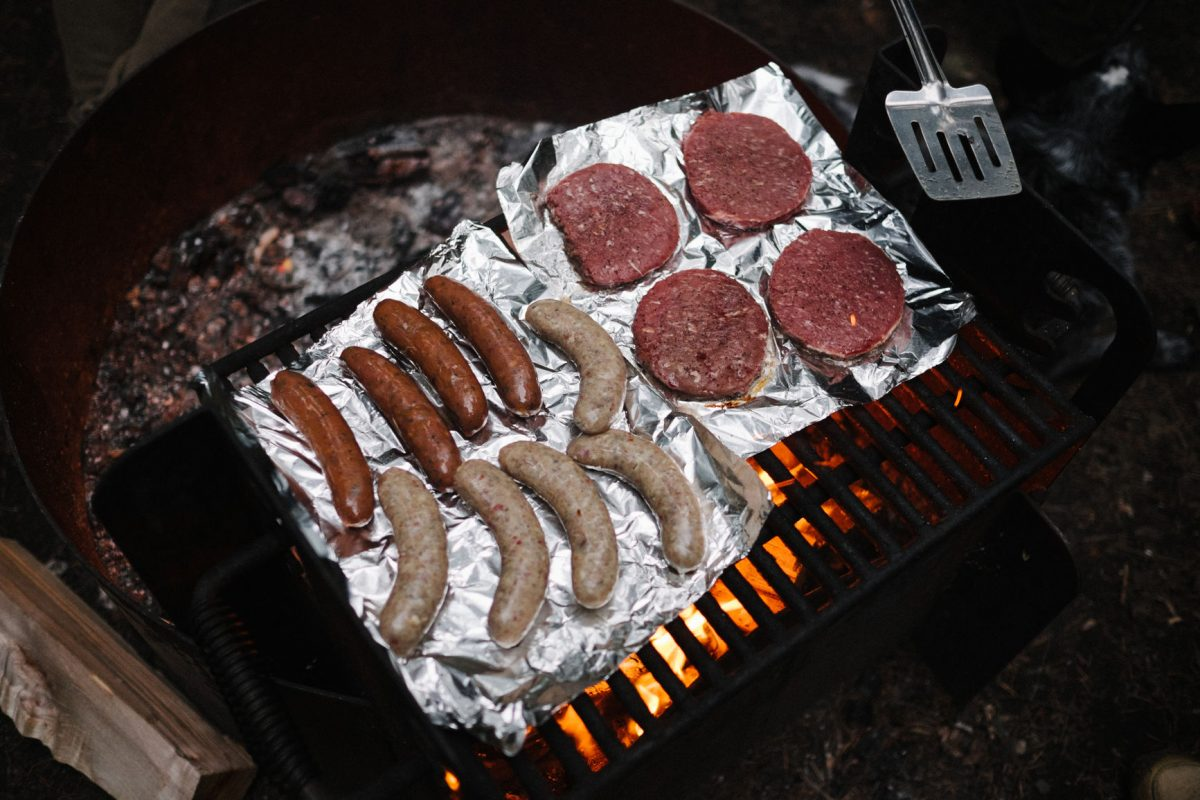 Hamburgers and bratwurst cooking over a campfire