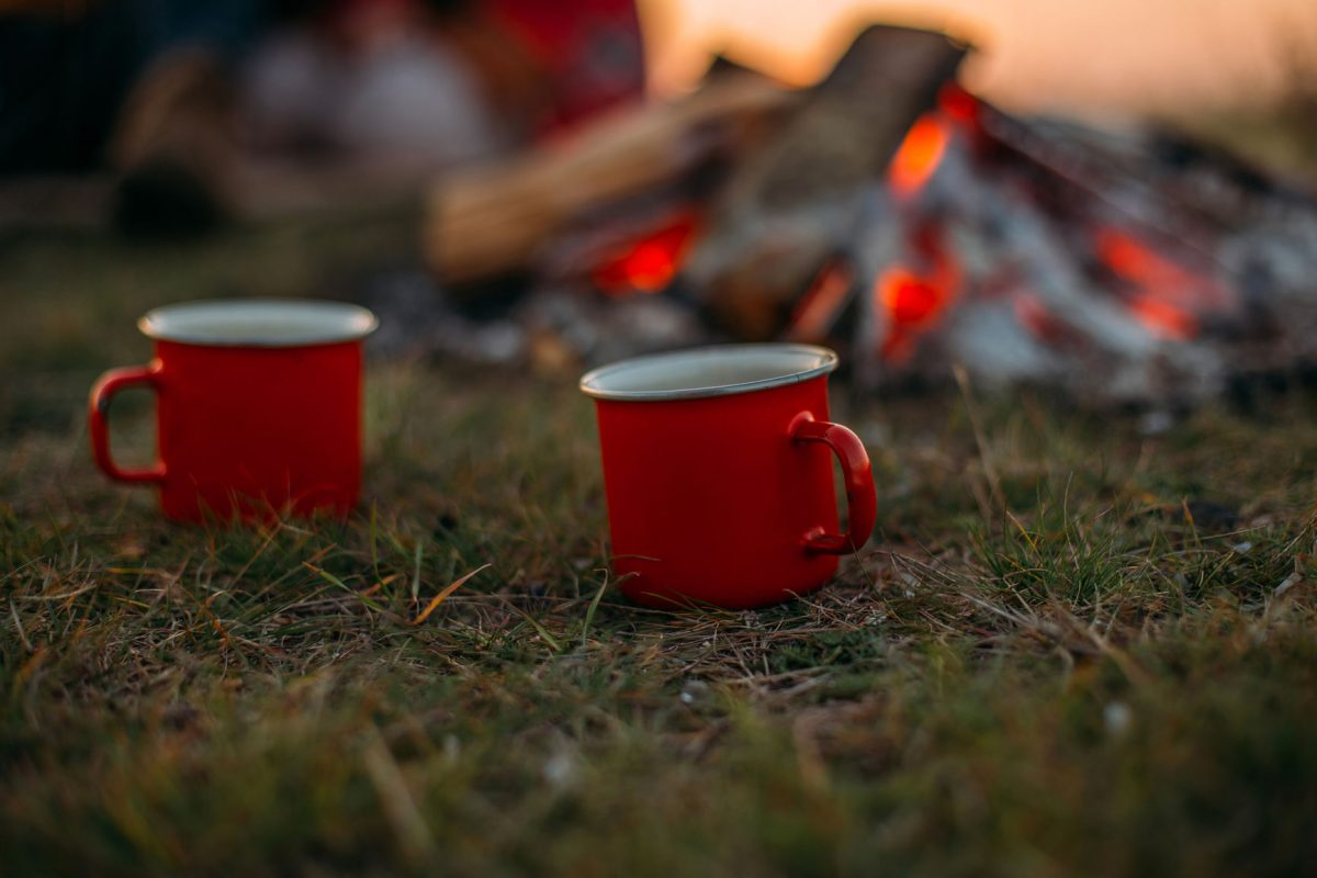 Two mugs in front of a dying campfire