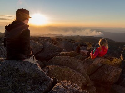 Couple watch sunset at Mt Kosciuszko summit