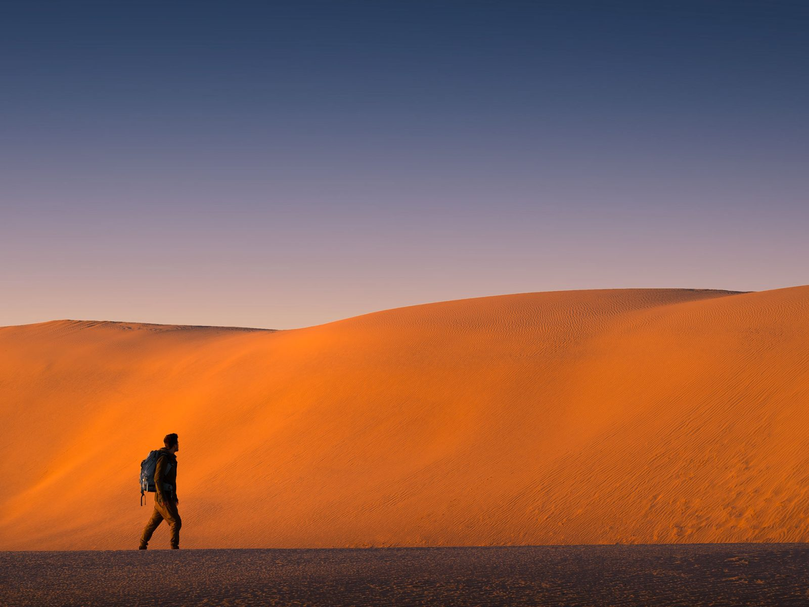 Man in front of large red sand dunes