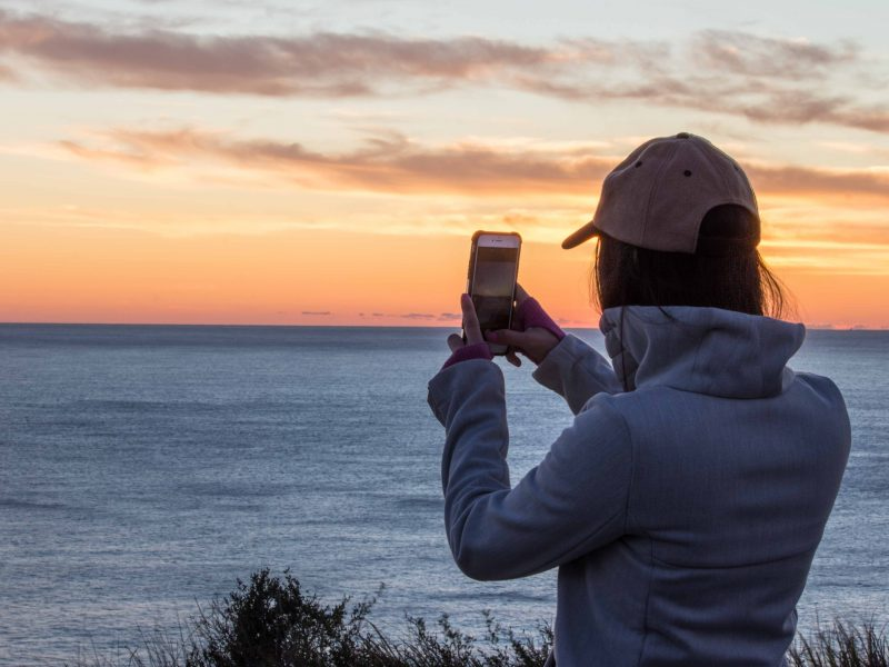 Girl taking a photo her phone of a sunset by the beach.