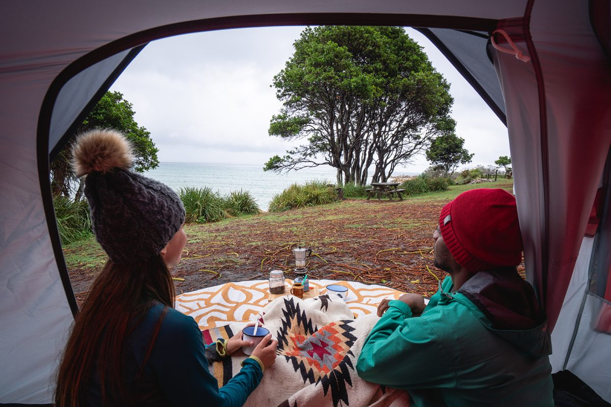 A couple (male and female) enjoying a hot drink looking out the sea at Trial Bay Gaol campground