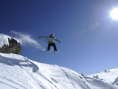 Snowboarder jumps off outcrop in Thredbo