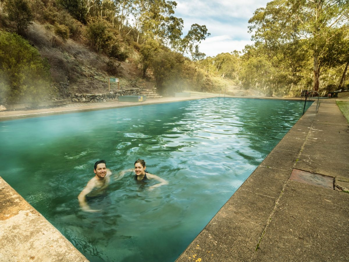 Couple in steamy outdoor Thermal pool, Yarrangobilly Caves