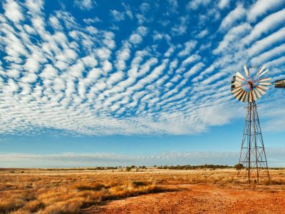 Old windmill, red dirt, plains and sky