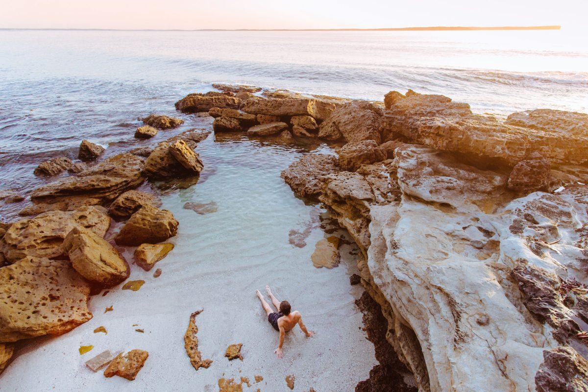 Teenager relaxing in a rock pool at Jervis Bay.