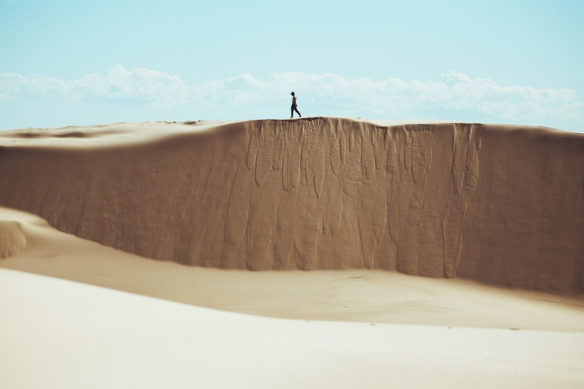 Man walking on the edge of Stockton sand dunes, Worimi National Park. Photo: Tim Clark