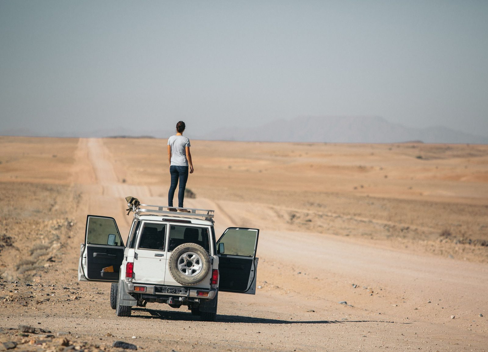 A woman stands on top of a car in a desert