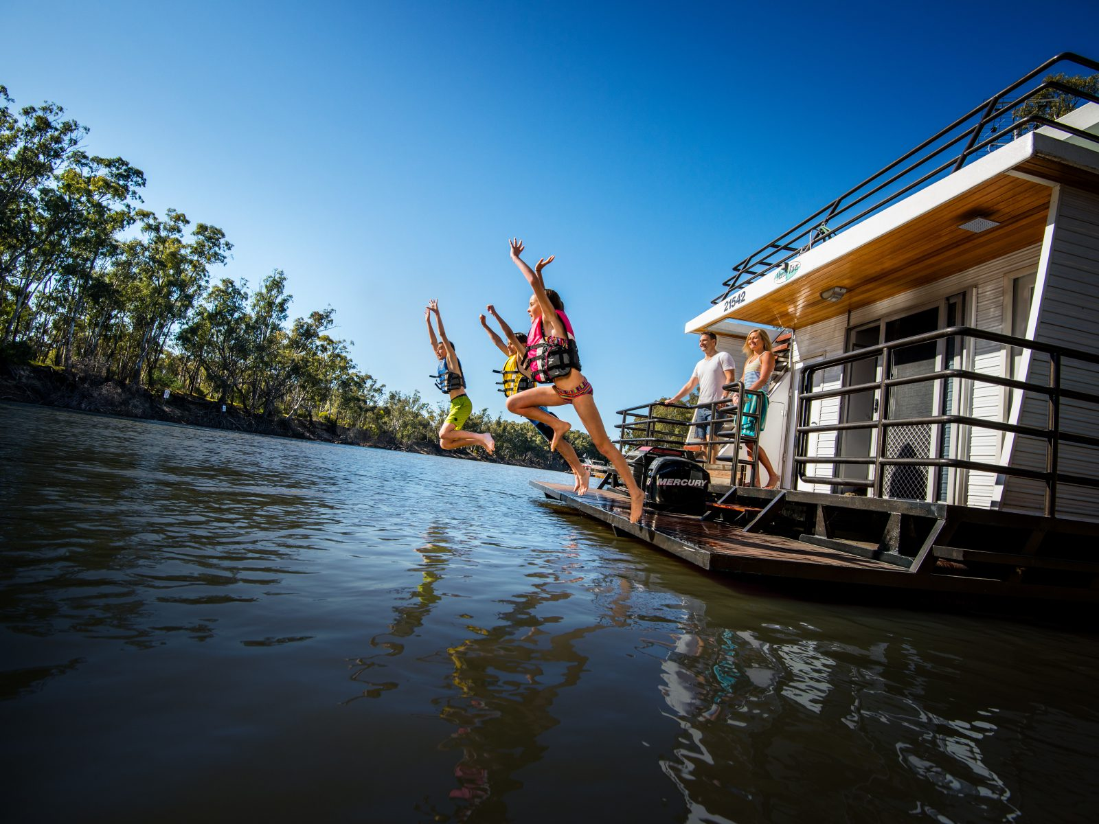 Children jump off a boat into the Murray River