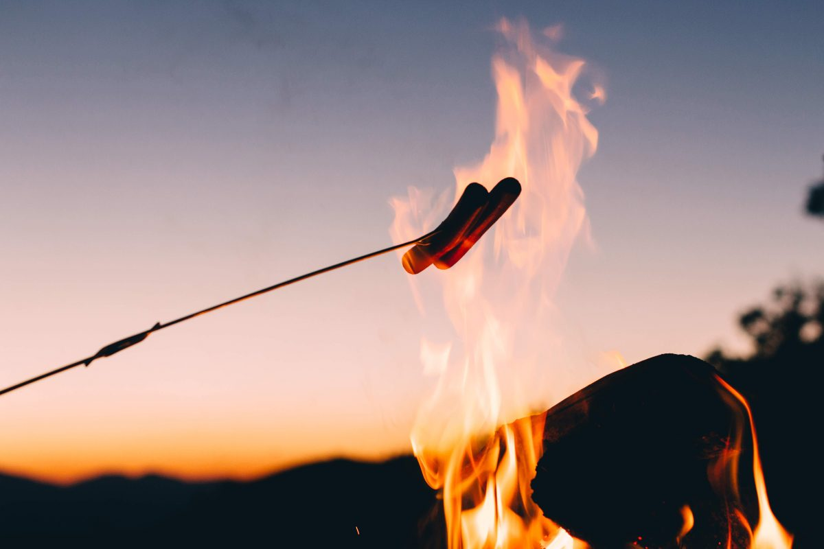 Sausages on stick held over flame