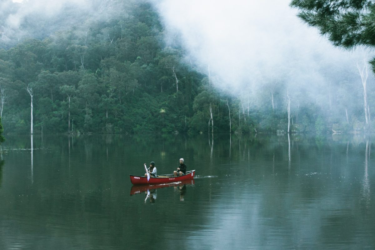 Couple on a canoe through the River surrounded by fog