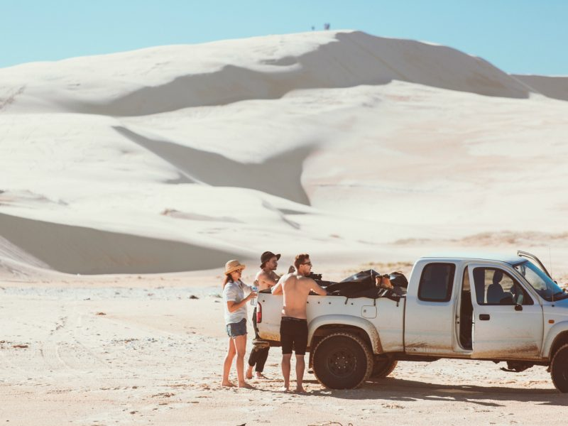 Three people with vehicle in the sand dunes