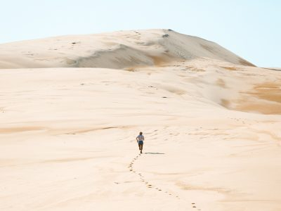 Person running up the Stockton sand dunes, Worimi National Park