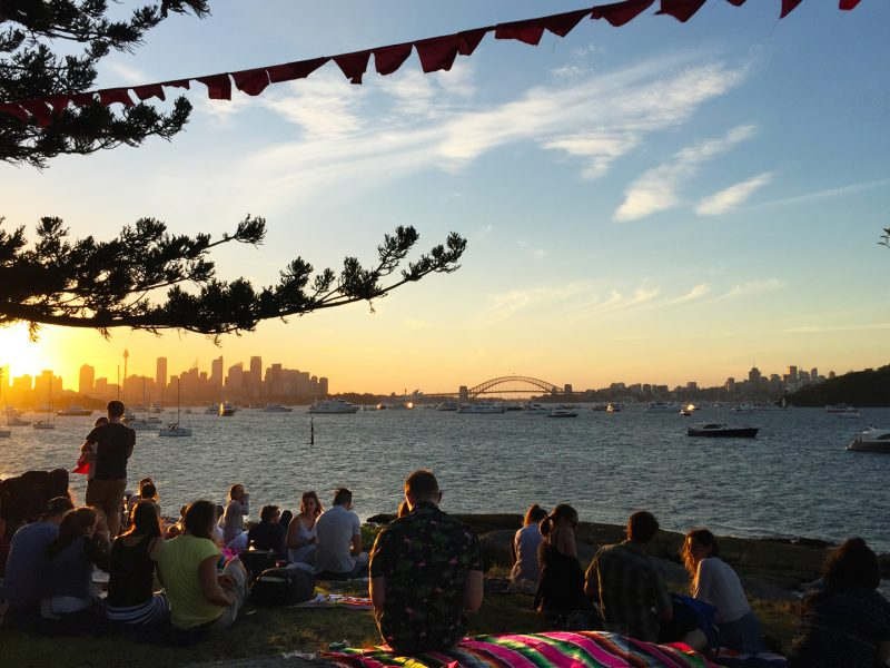 People relaxing at sunset before the Sydney Harbour New Year's Eve fireworks at Shark Island, Sydney Harbour National Park. Photo: Matthew Mannall