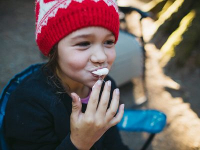 Child eating a marshmallow by a campfire