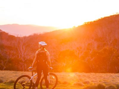 Person standing in the sunset with a mountain bike on the Thredbo Valley track, Kosciuszko National Park. Photo: Boen Ferguson/DPIE