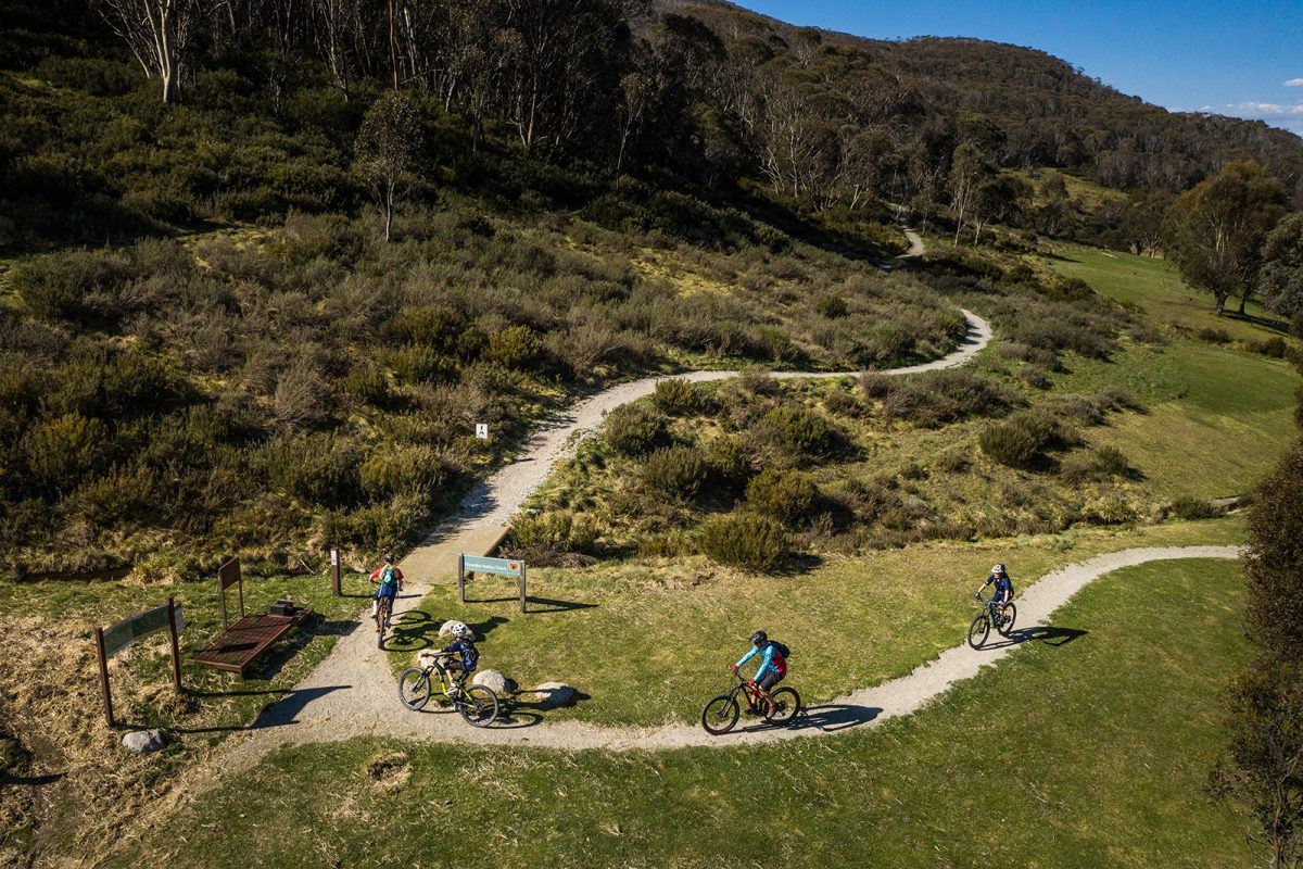 Aerial view of a family of four riding the Thredbo Valley Track.