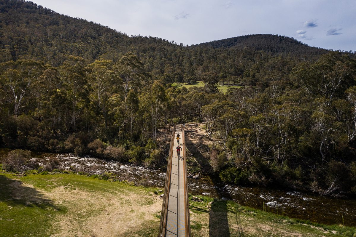 Aerial view of two guys riding the final bridge of the Lower Thredbo Valley track