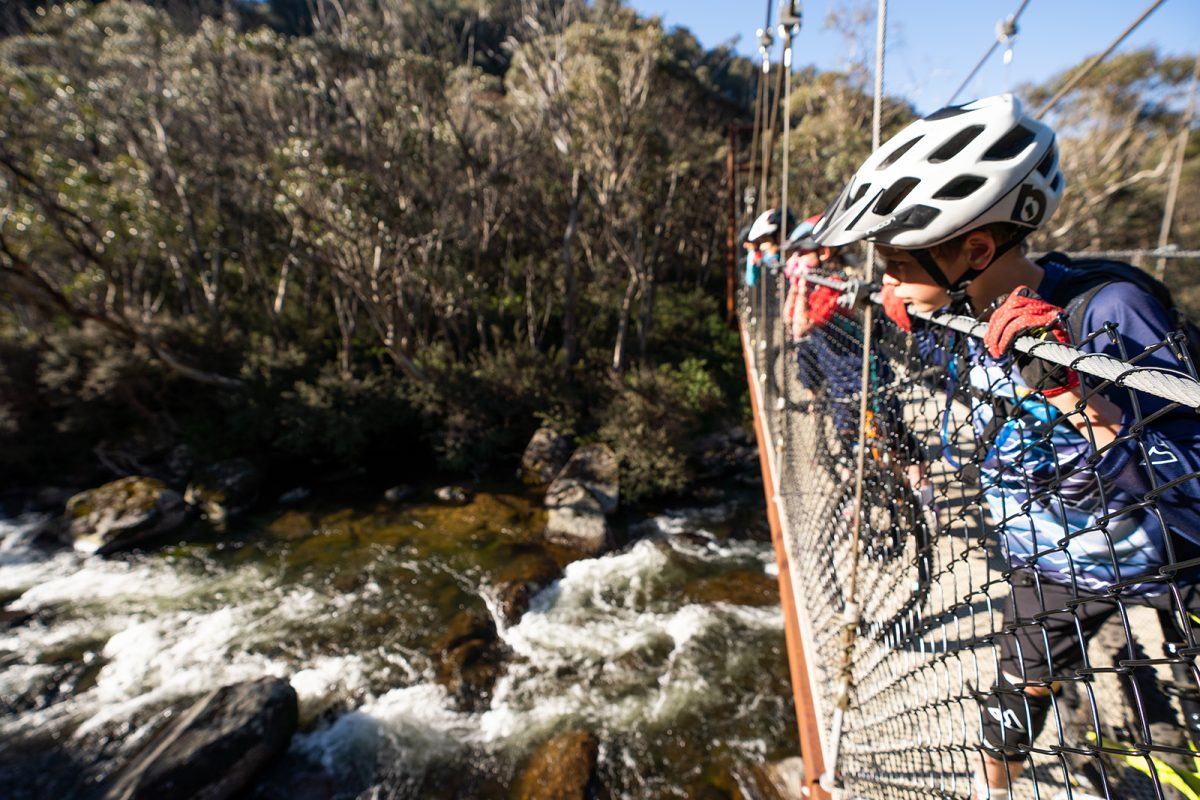 People peering over the bridge to look at the Thredbo Valley river below