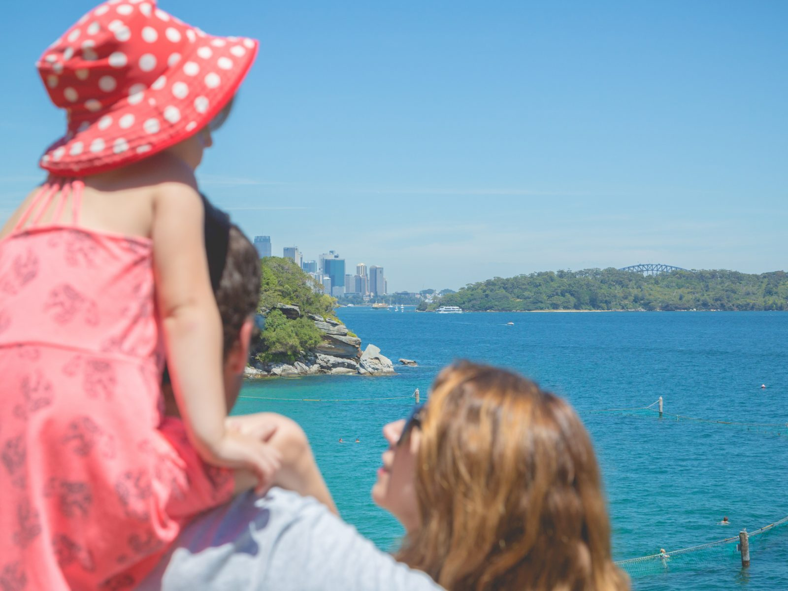 Family looking at view of Sydney from Shark Beach, Sydney harbour National Park