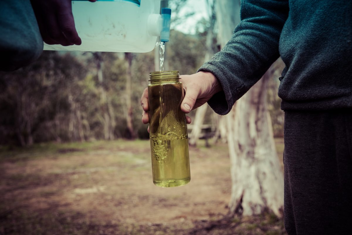 People filling a water bottle in Kosciuszko National Park. Photo: Person admiring view of Snowy Mountains, Kosciuszko National Park. Photo: Daniel Parsons/DPIE