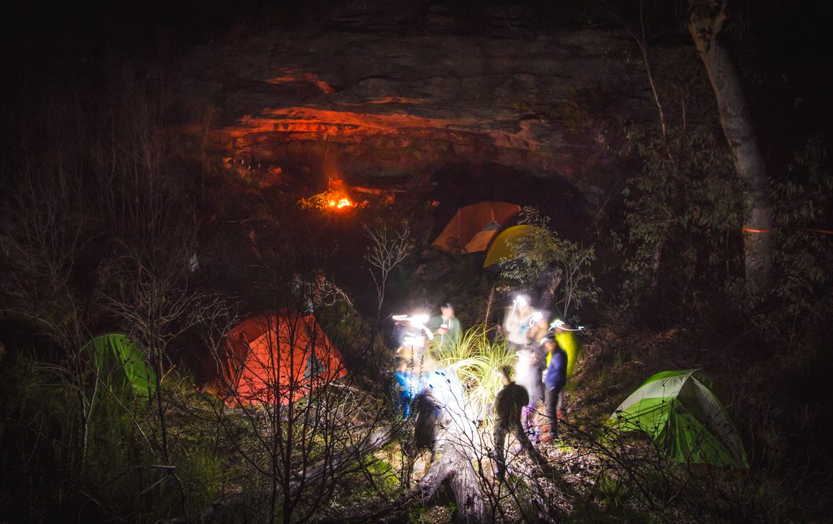 Group of people at a campground in the night. Photo: Henry Brydon