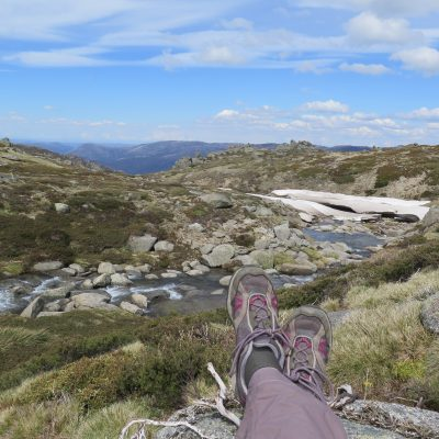 Hiker relaxing on the Thredbo to Mount Kosciuszko walk in Kosciusazko National Park. Photo: Elinor Sheargold/DPIE