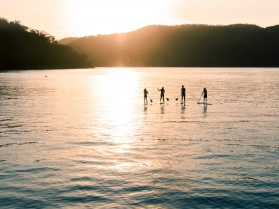 Two people stand-up paddleboarding at The Basin in Ku-ring-gai Chase National Park