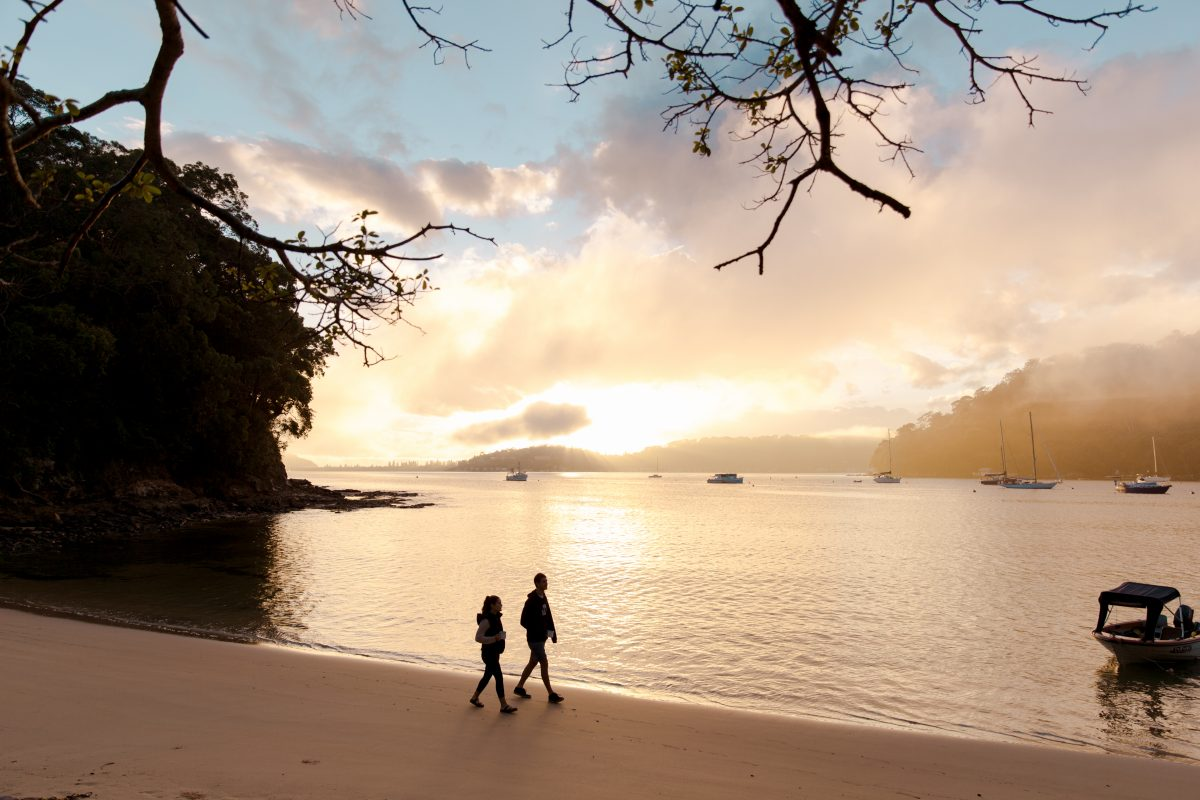 Couple walking along a beach in Ku-ring-gai Chase National Park