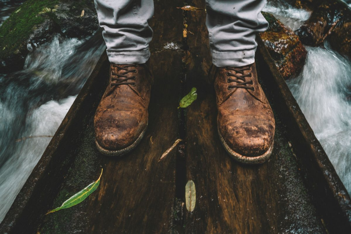 Pair of hiking boots on a bridge over a flowing creek. Photo: Branden Bodman/OEH