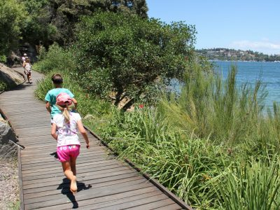 Children running on the boardwalk Hermitage foreshore walking track in Sydney Harbour National Park. Photo: John Yurasek/OEH