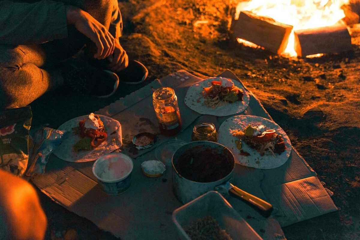 Group of people eating around a campfire at The Basin campground in Ku-ring-gai Chase National Park