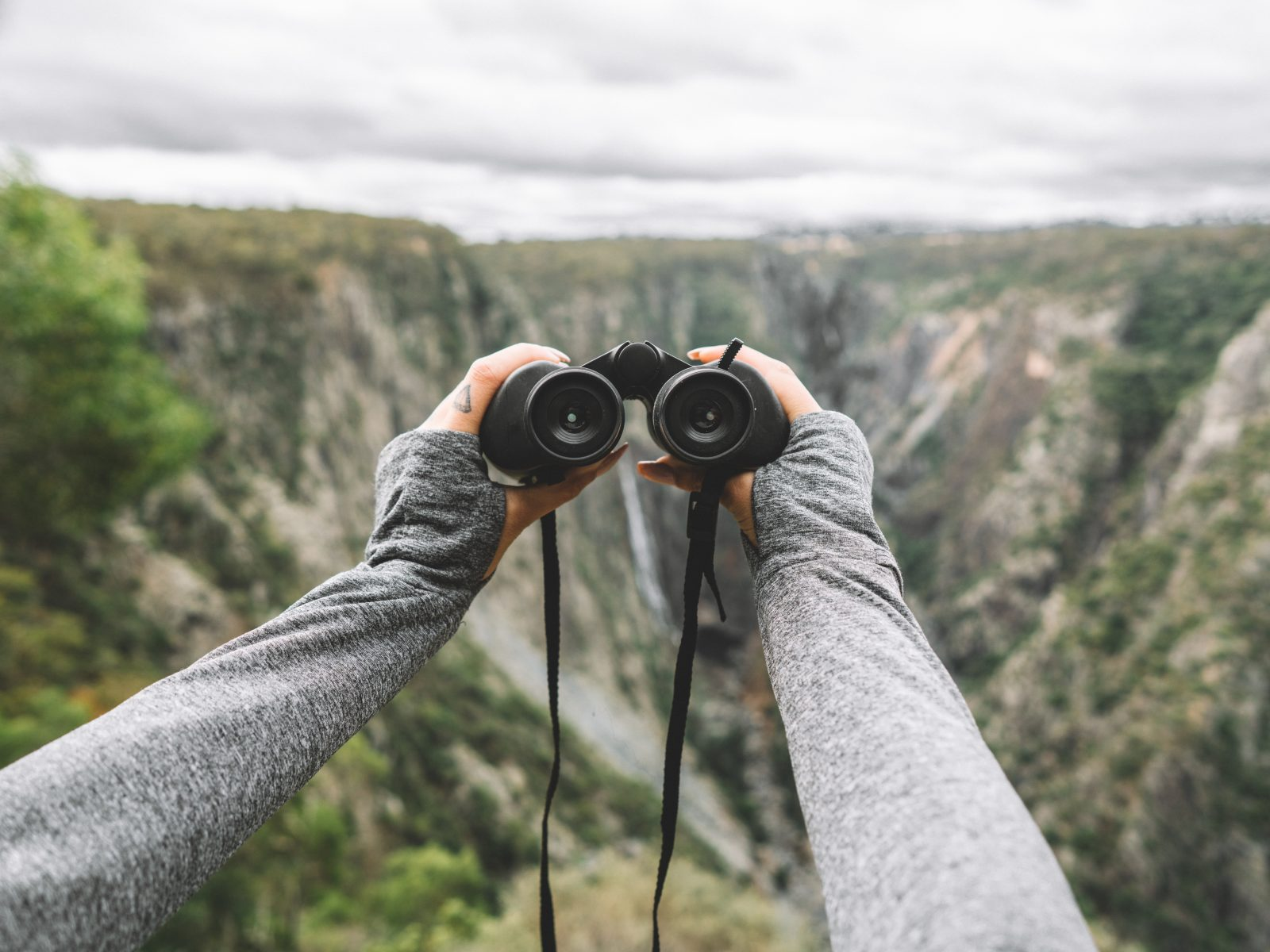 Holding binoculars looking for waterfalls