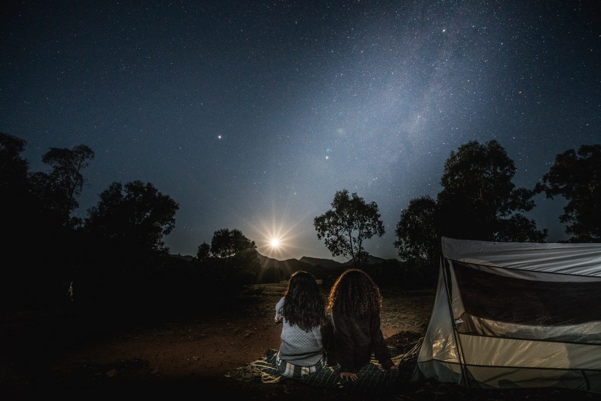 Two people camping under the stars at Warrumbungle National Park. Photo: Robert Mulally/OEH