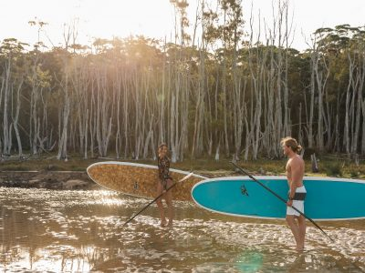Two people taking their paddleboards to Durras Lake in Murramarang National Park. Photo: Melissa Findley/OEH