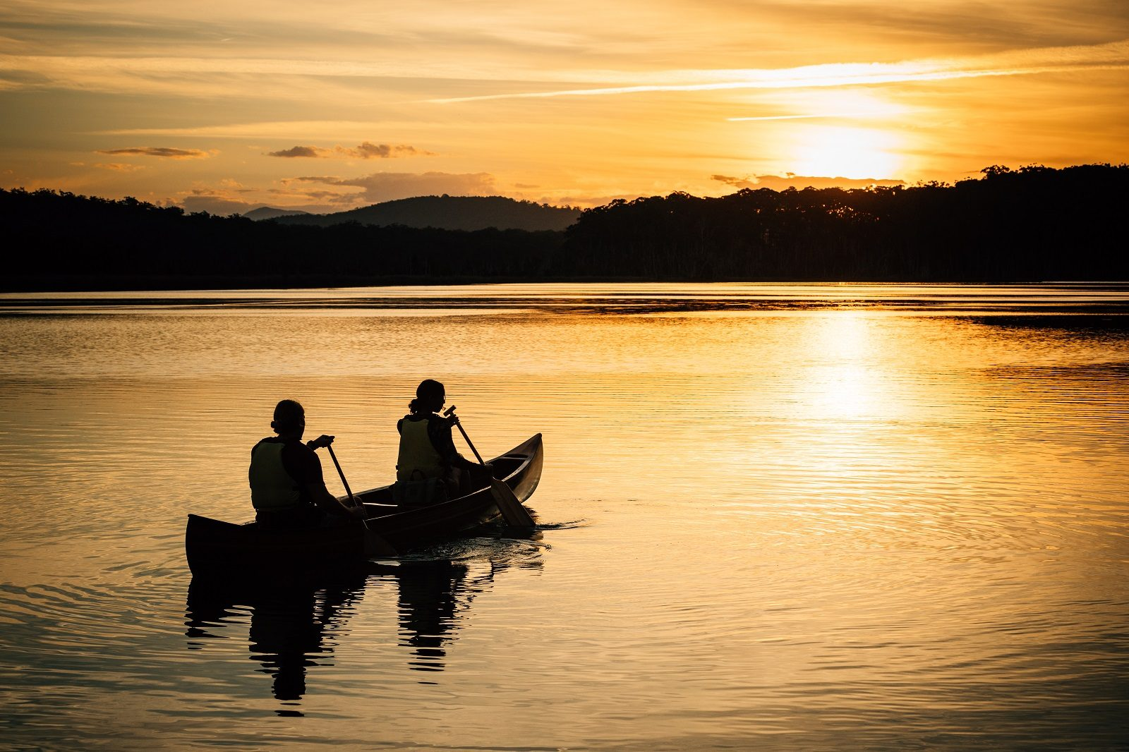 Silhouette of 2 people in a canoe on a Lake, in a national park at sunset.