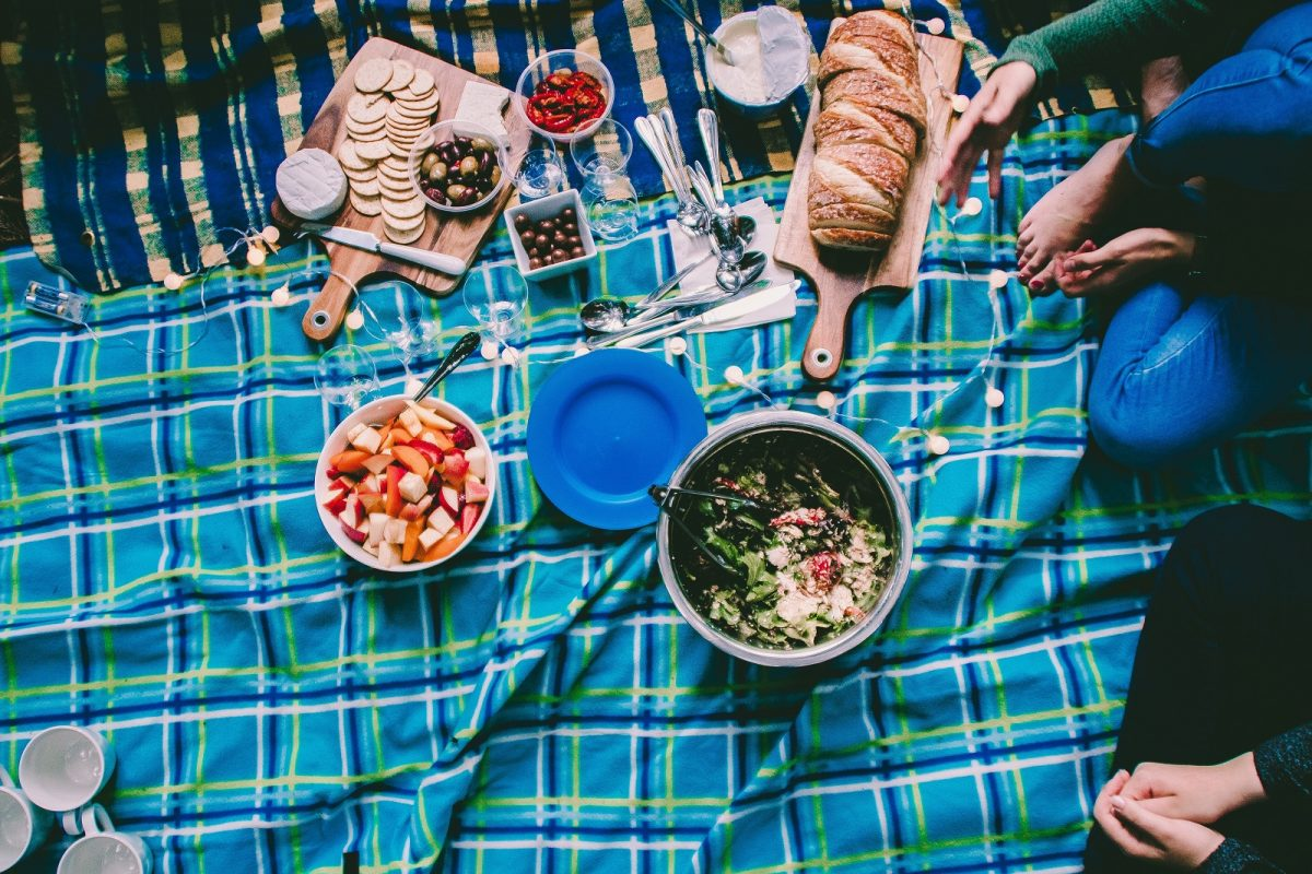 Looking down on a picnic of olives, sun dried tomatos, crackers, bread and salads on a picnic blanket