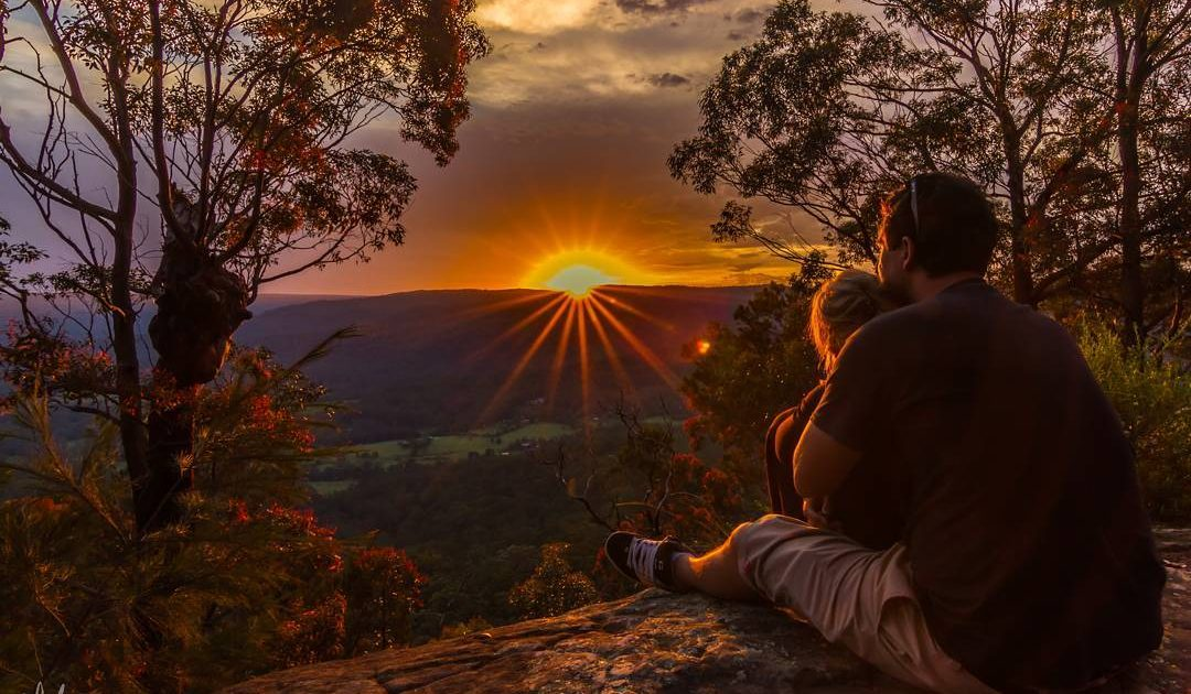 Two people sitting at Monkey Face lookout in Watagans National Park. Photo: Matthew Landesmann