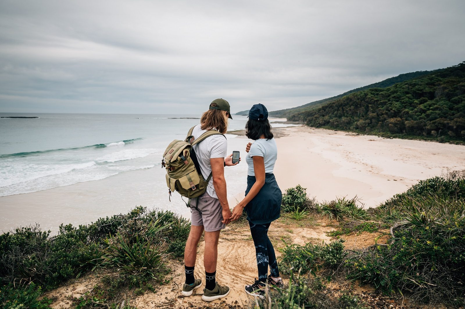 A couple holding hands looking at their mobile device with the view of the beach in front of them at Murramarang National Park. Photo: Melissa Findley/OEH