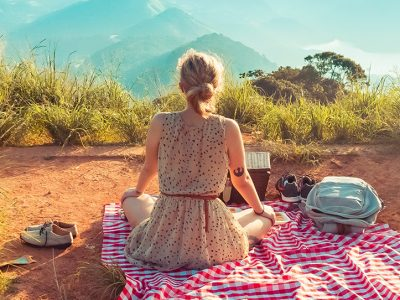 Woman sitting on a picnic blanket with a mountain view in front of her