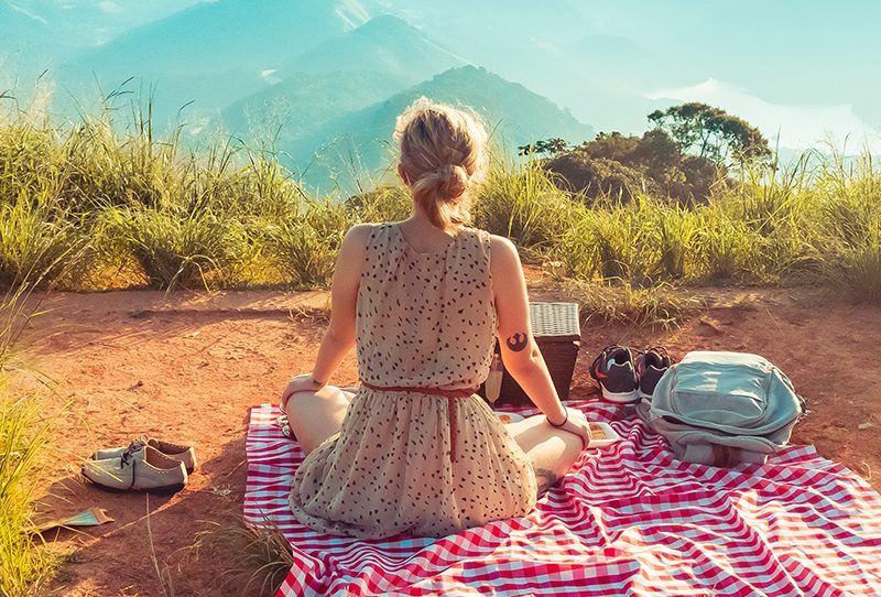 Woman sitting on a picnic blanket with a mountain view in front of her. Photo: William Justen De Vasconcellos