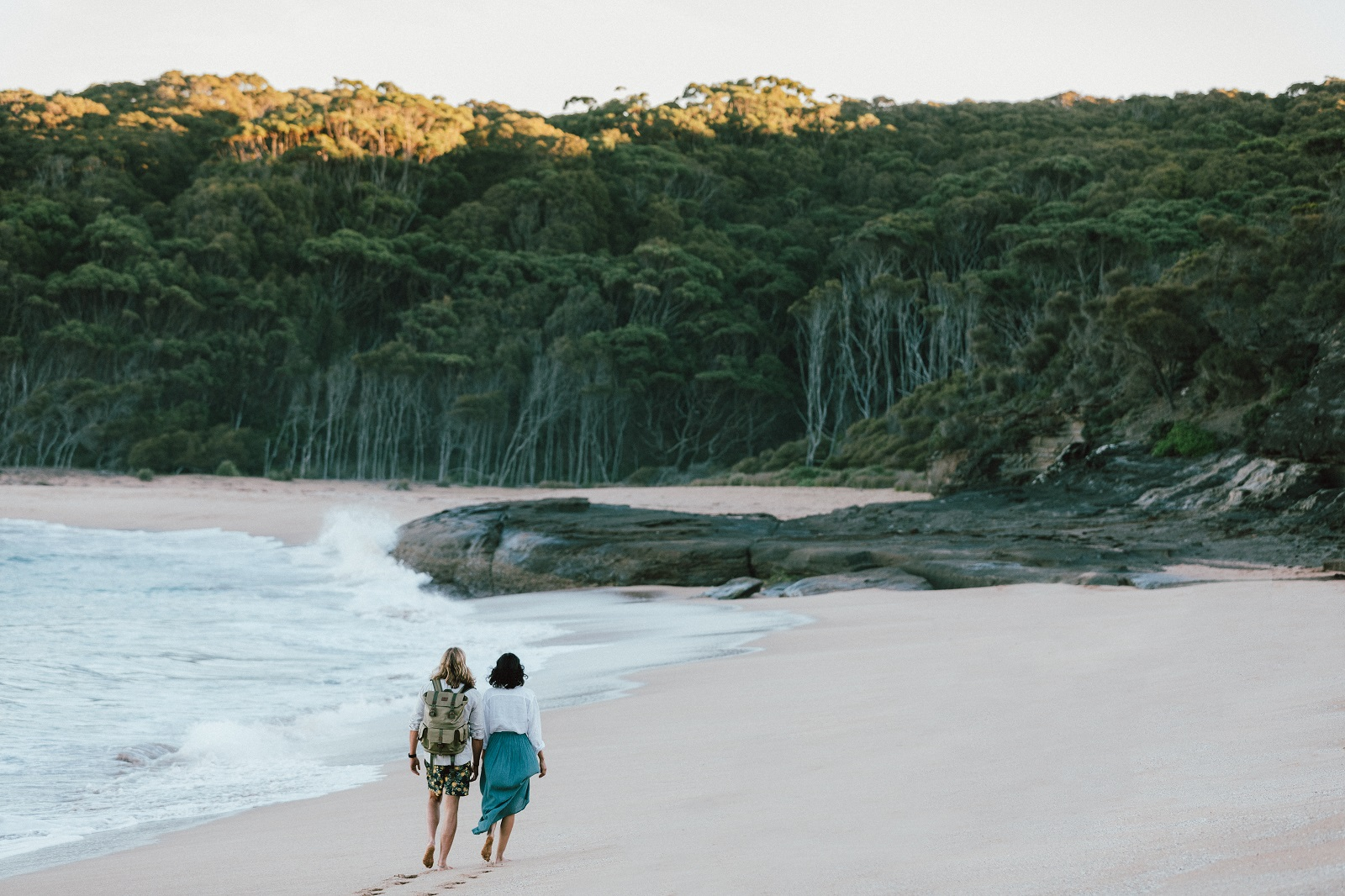 A man and woman walking along Emily Miller Beach in Murramarang National Park