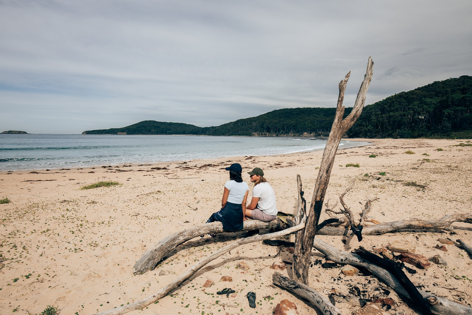 Couple sitting at Pebbly Beach in Murramarang National Park. Photo: Melissa Findley/OEH
