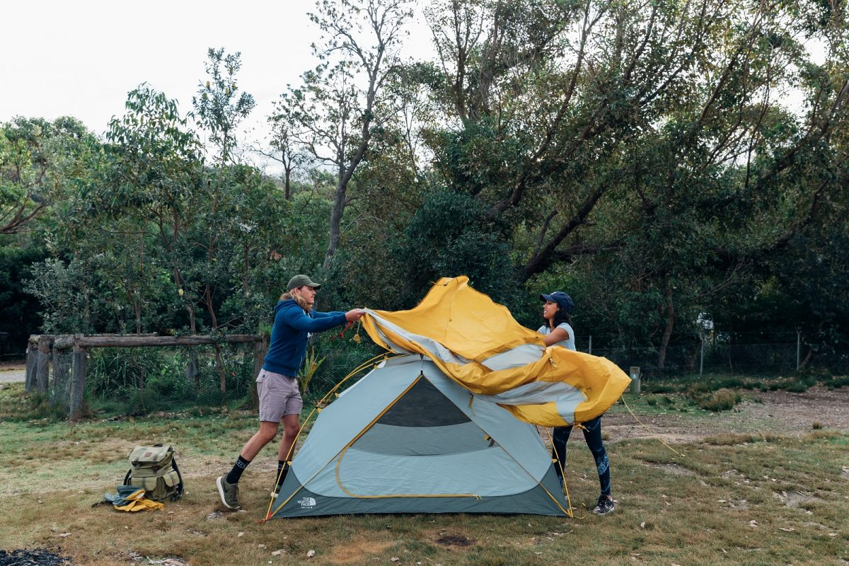 A woman and man setting up the tent at Pretty Beach campground. Photo: Melissa Findley/OEH