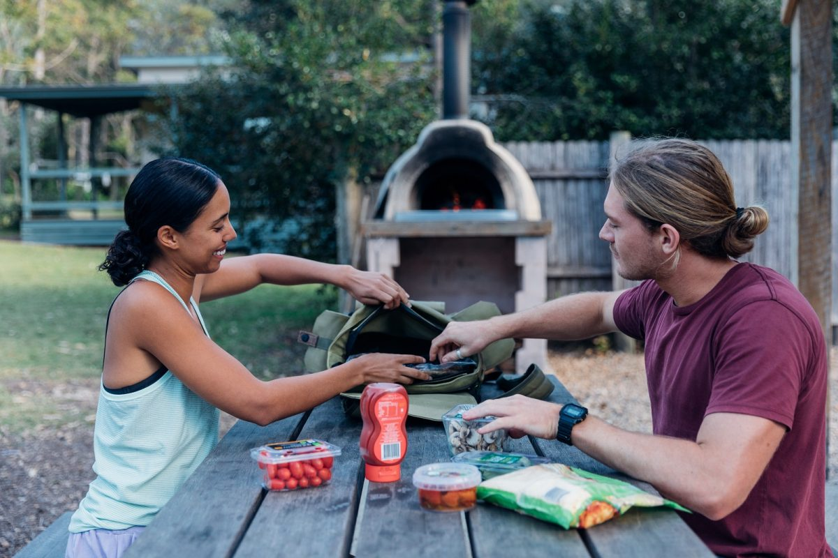 A man and woman getting out ingredients to make a pizza in a woodfired oven in Depot Beach cabins and campground
