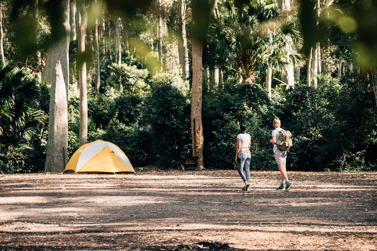 A woman and a man walking to a tent at Depot Beach campground, Murramarang National Park. Photo: Melissa Findley/OEH